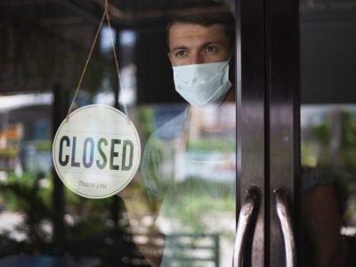 Chef in safety mask hanging up sign closed on restaurant door.